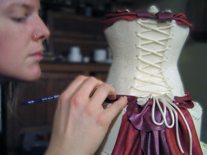 Decorating a wedding cake with corset and fabric